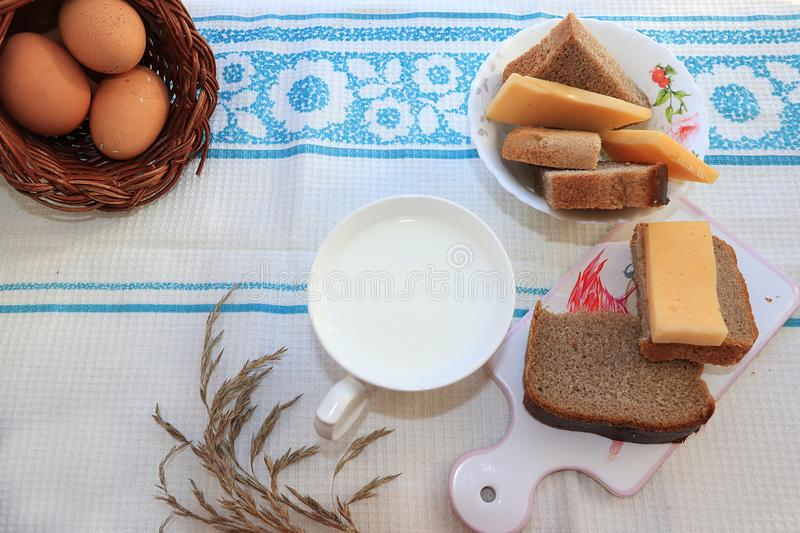 Country breakfast, milk and cereal bread, slices of cheese and fresh eggs in a basket royalty free stock image