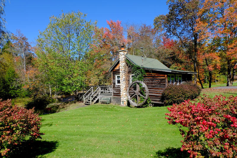 Country Cabin in Autumn. Country cabin with decorative wheel and stone chimney surrounded by brilliant colors on a sunny autumn day stock image