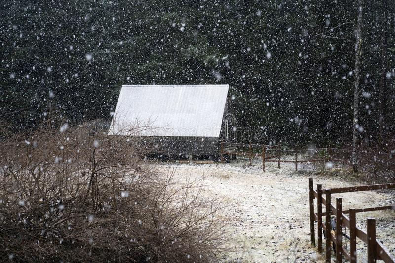 Country cabin in snow. First snow falling on a country cabin with a rustic fence royalty free stock photography