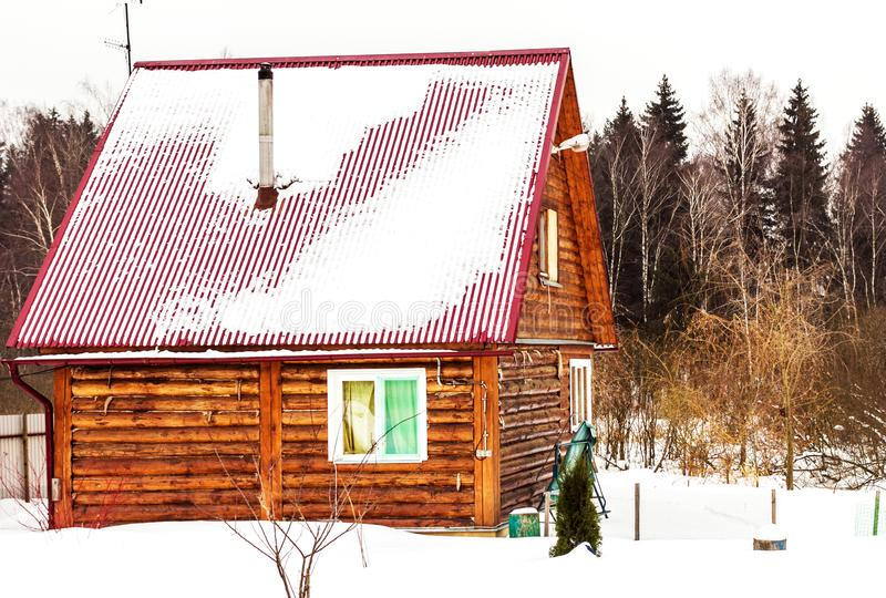 Country cabin in winter snow. Wooden pretty country cabin in snow at winter cloudy day royalty free stock images