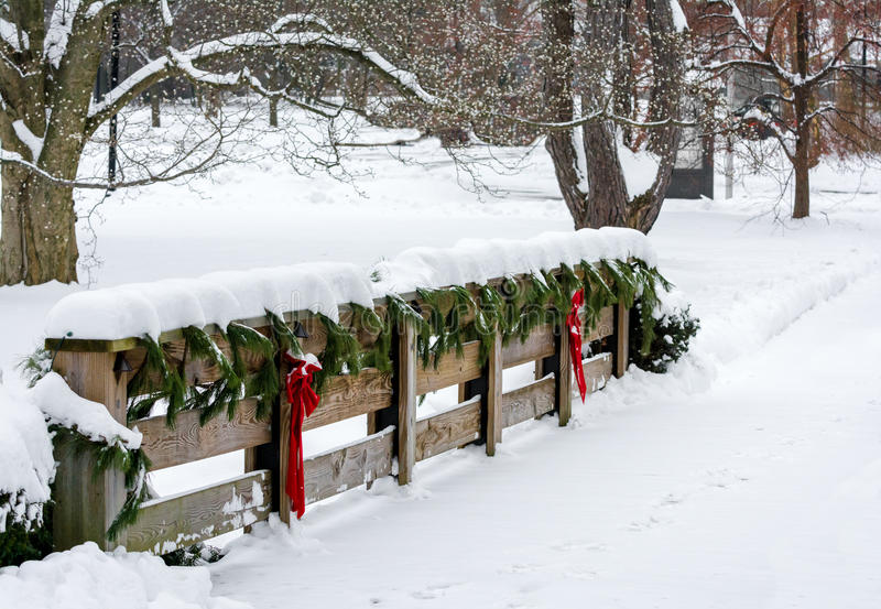 Country Christmas Scene. Winter scene with a snow covered decorative wooden fence with evergreen pine trim and red bows and ribbons royalty free stock images