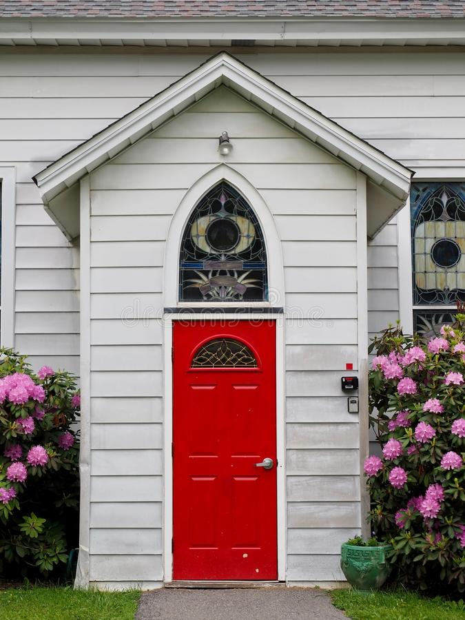 Country Church Entrance With Enclosed Alcove Entrance. A country church with white siding, red door, reuleaux arched window, and enclosed alcove entrance with stock image