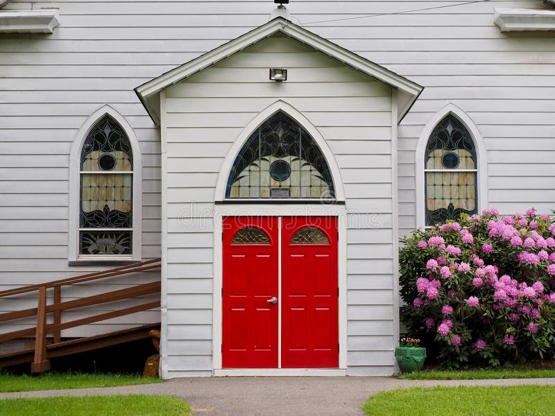 Country Church Entrance With Enclosed Alcove Entrance. A country church with white siding, red doors, reuleaux arched windows, handicap entrance and enclosed stock images