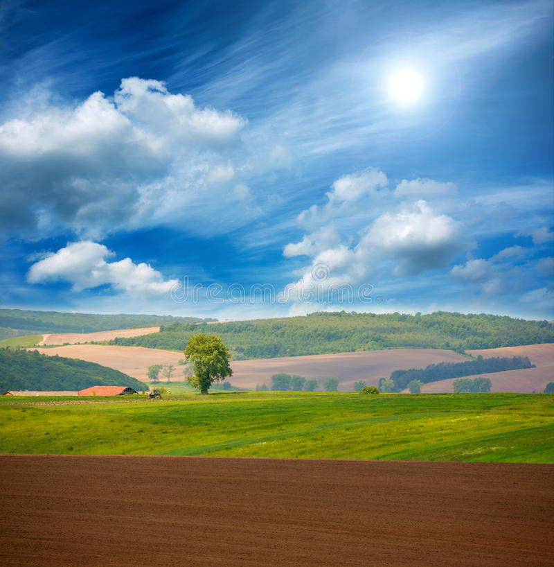 Country dry plowed earth agricultural green farmland on blue sky. Country landscape dry plowed earth agricultural green farmland on blue sky stock images
