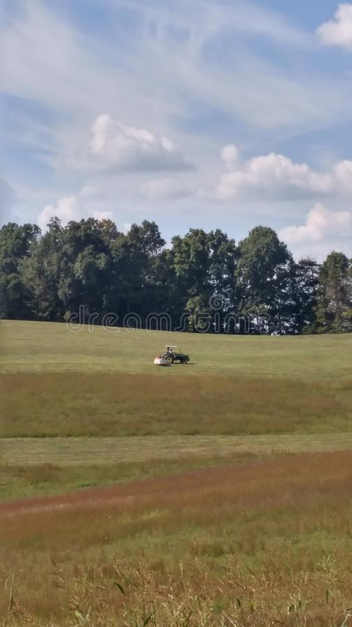 Country. Farmer cutting grass stock photography