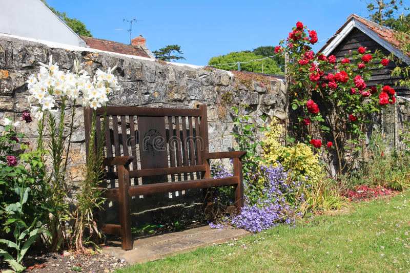 Country Garden Seat. Roses and lilies surround and English Country garden Seat stock image