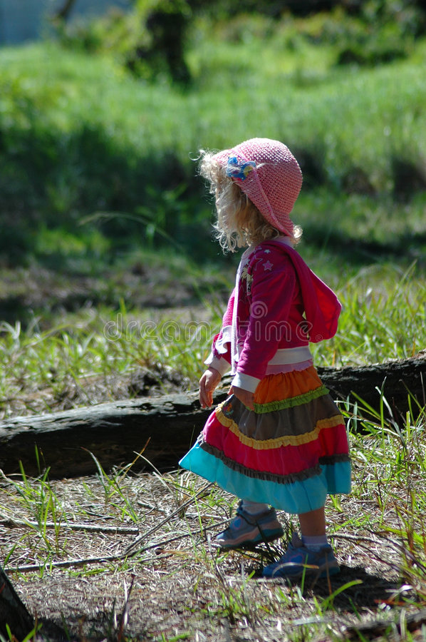 Country girl. A colorful cute caucasian gypsy country girl toddler with a pink hat walking and watching nature and other kids in the forest outdoors stock photography