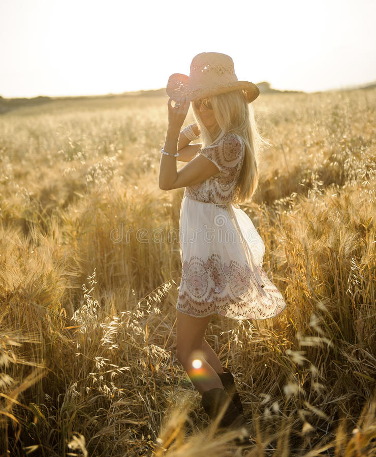 Country girl in hay field 2. A beautiful country girl tilting her hat in a cornfield at sunset royalty free stock image