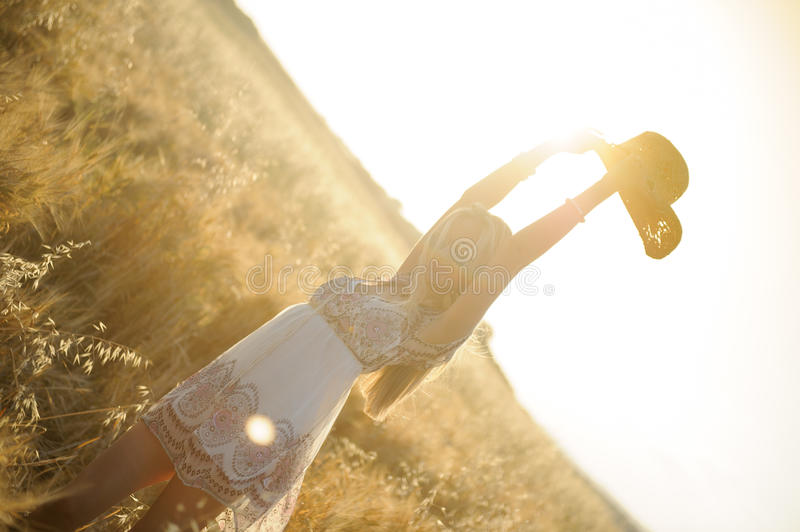 Country girl in hay field. A beautiful country girl raising her hat in a cornfield at sunset royalty free stock photos