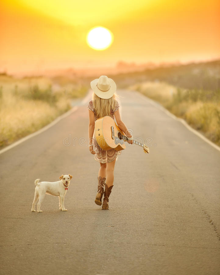 Country girl walking down a sunset road. A country girl walking down a road at sunset with her guitar and her dog