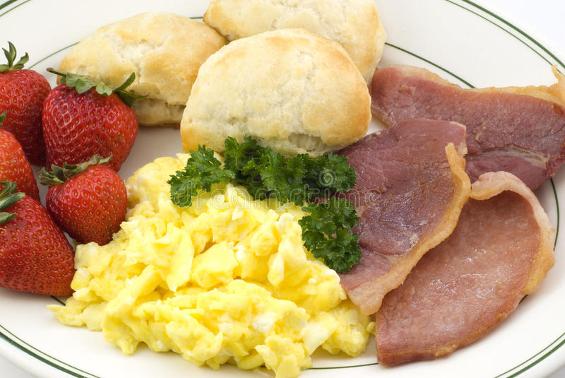 Country Ham Breakfast Platter. A homemade breakfast with country ham slices, fresh baked biscuits, scrambled eggs and strawberries on a platter, closeup stock image