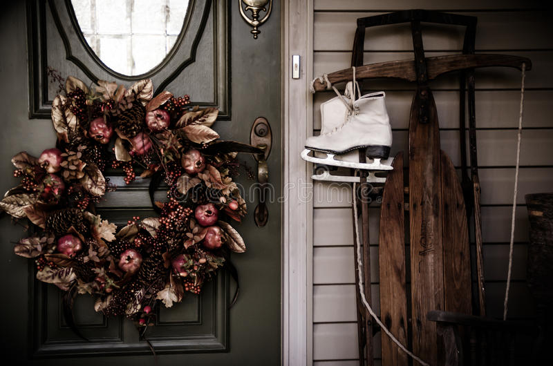 Country home with sled skates. Country home with classic sled, ice skates and wreath stock photos