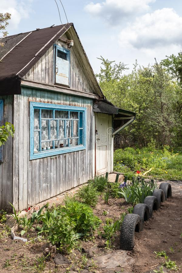Country house with cultivated land surrounded by greenery in spring in Russia. Russian dacha. Country house with cultivated land surrounded by greenery in spring stock photo