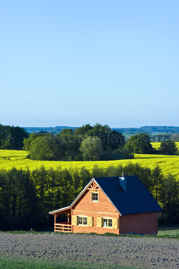 Country house in a field. A single, wooden country house standing in a beautiful scenic countryside royalty free stock images