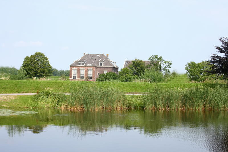 Country house. Lonely old House, with a body of water in the foreground stock image