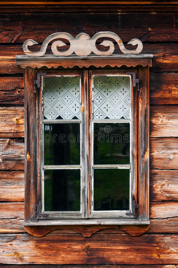 Country house window. Rustic wooden house window with simple ornaments and courtain stock photography