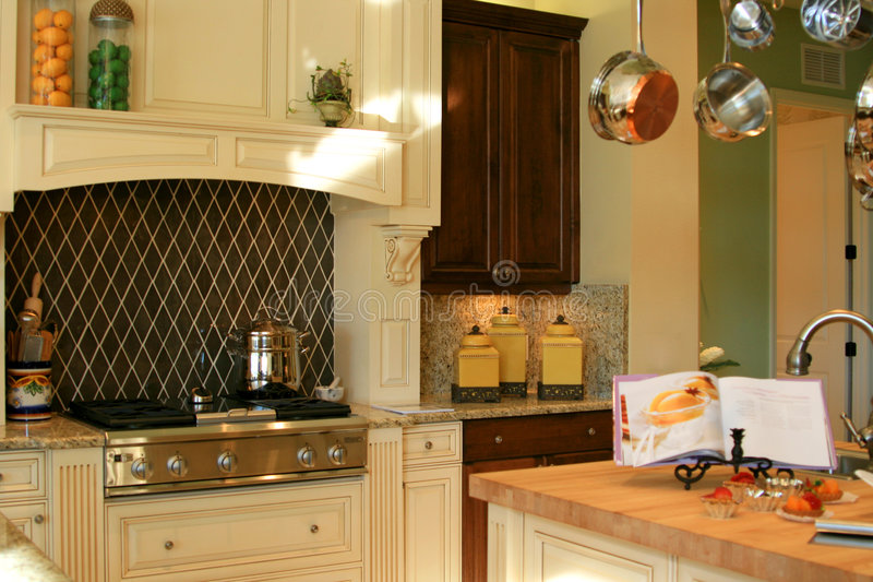 Country Kitchen. Contemporary country kitchen in soft colors of beige and green, granite countertop, wooden cabinets and island with cutting board top