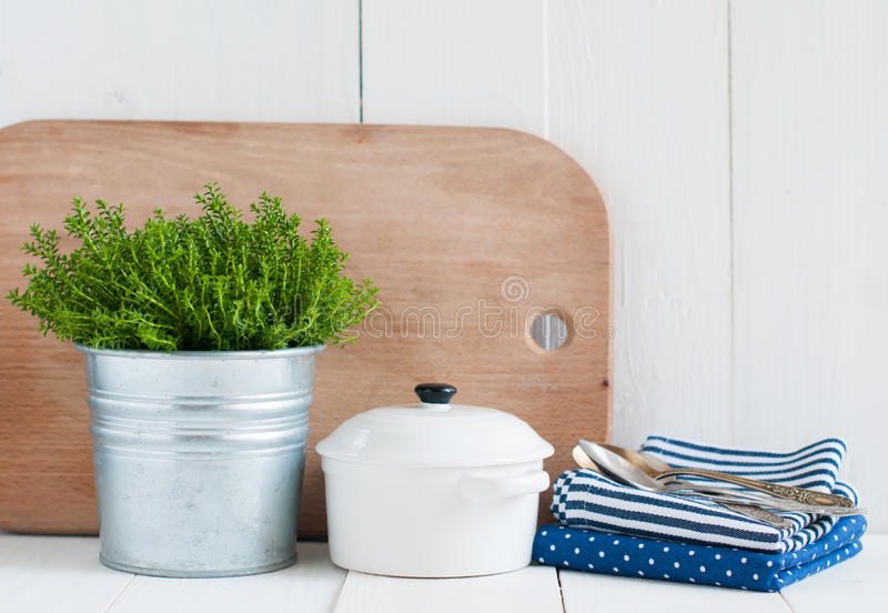 Country kitchen decoration. Cottage life, country kitchen decoration: a house plant in a metal pot, kitchen pottery, utensils and napkins on white painted board stock photography