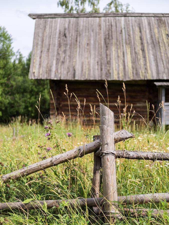 Country landscape with old rustic wooden fence and log house. Rural landscape with elements of wooden architecture royalty free stock photo