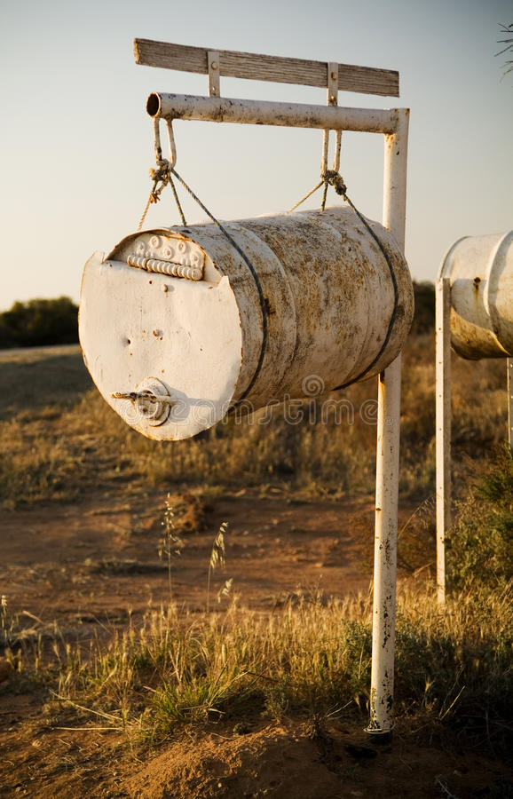 Country Letterbox / Mailbox. White rusting barrel hanging from a pole forms a country letterbox / mailbox royalty free stock images
