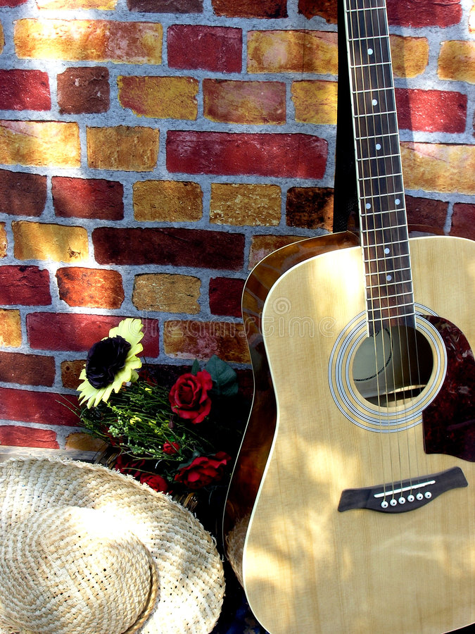 Country music. Guitar, flower and country hat on the porch resting after short country music concert for friends during weekend stock photo