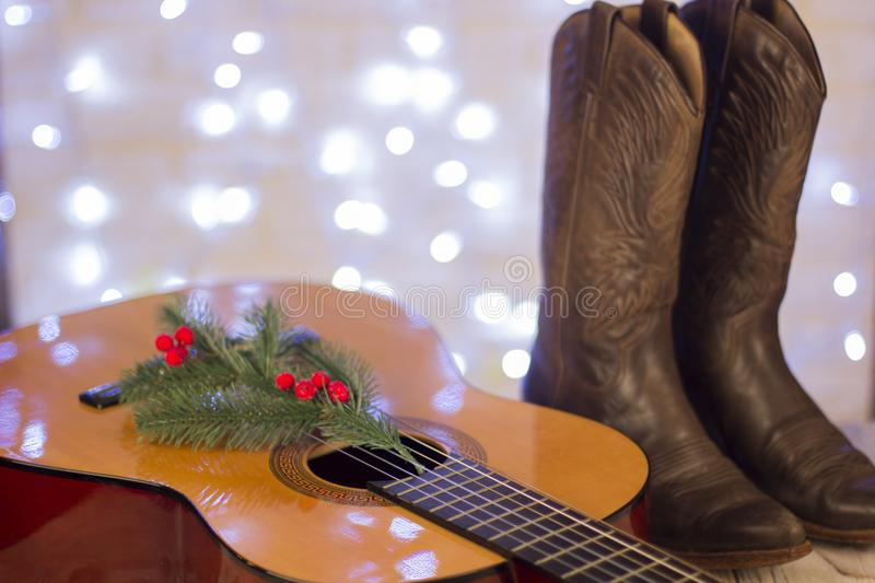 Country music christmas with acoustic guitar and cowboy shoes stock photo