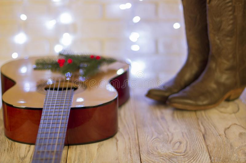 Country music christmas with guitar and cowboy shoes. Country music christmas with acoustic guitar and cowboy shoes on wood table royalty free stock image