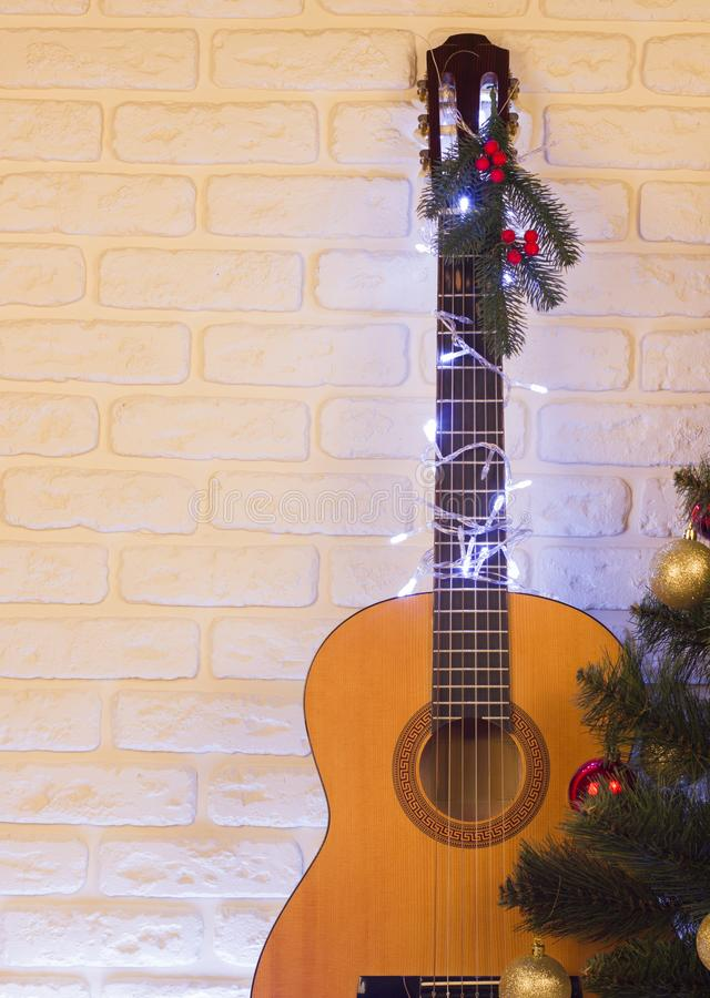 Country music christmas background with guitar on brick wall. For text stock photography