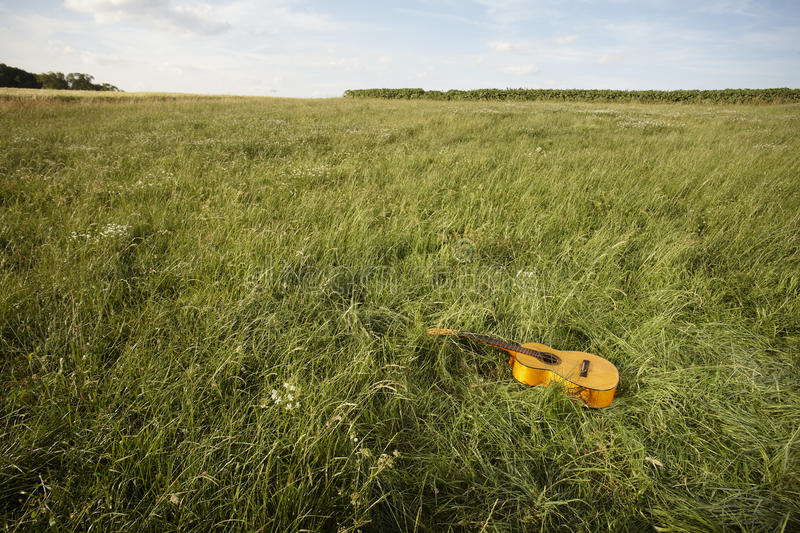 Country music concept. Acoustic wooden guitar lying by itself in a grassy field in a country music concept stock image