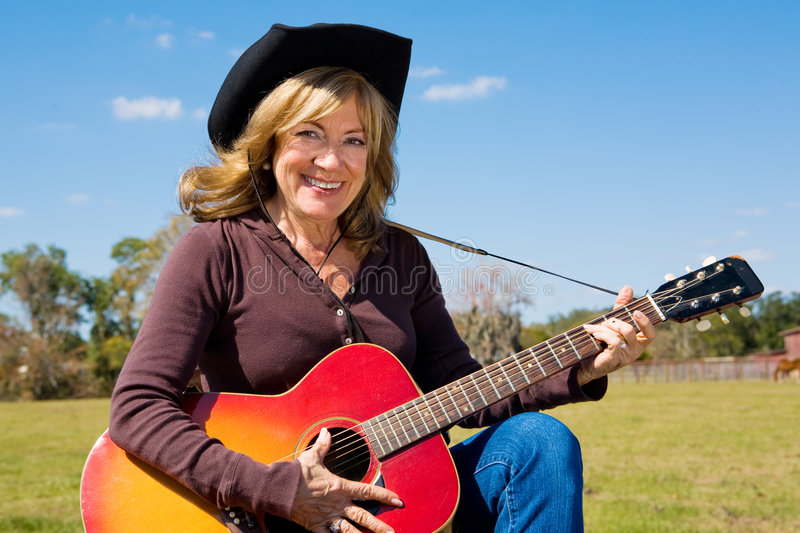 Country Music Cowgirl. Beautiful mature cowgirl plays country music on the farm royalty free stock images