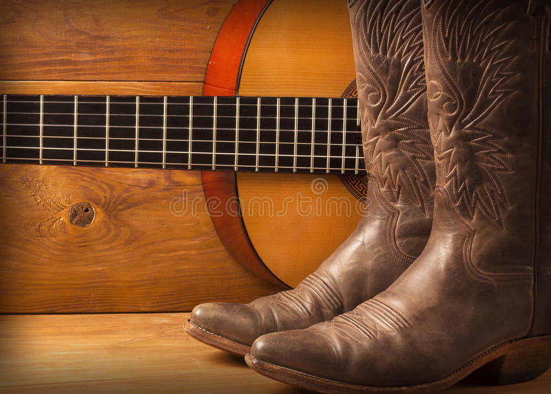 Country music with guitar and cowboy shoes. American Country music with guitar and cowboy shoes on wood royalty free stock photo