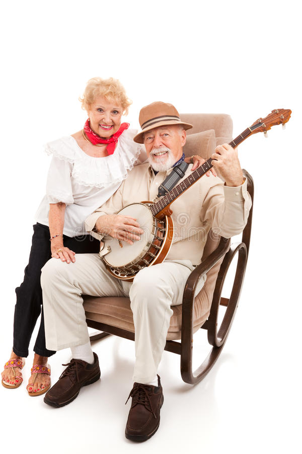 Country Music Seniors. Senior couple enjoys singing and playing country music. Isolated on white stock photo