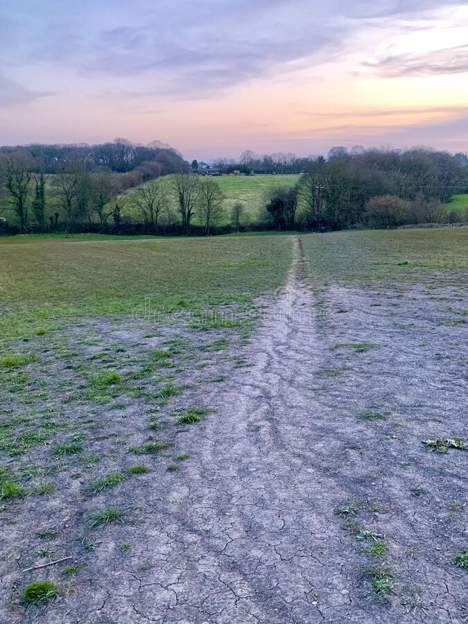 Eroded country path. A country path across a grassy field eroded by use stock photography