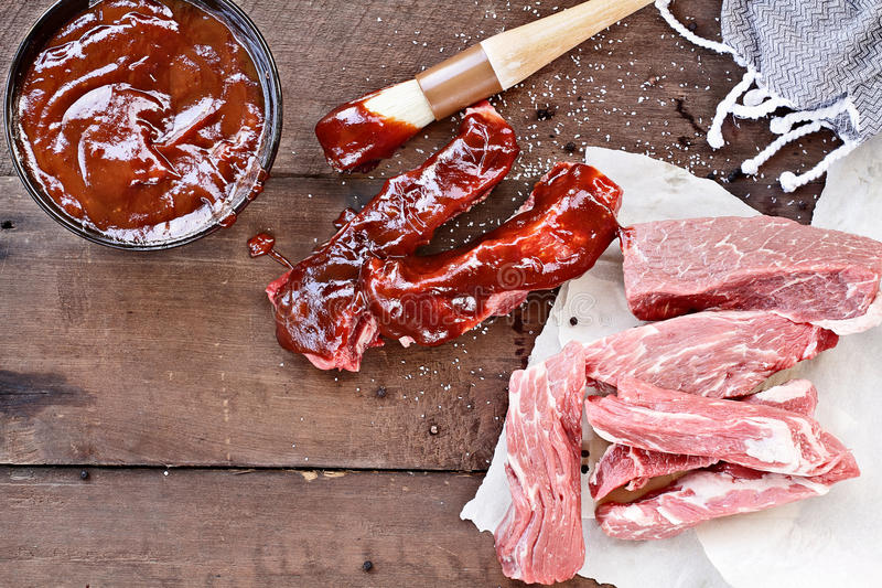 Country Ribs and Barbecue Sauce. Country ribs with barbecue sauce and basting brush over a rustic table stock images