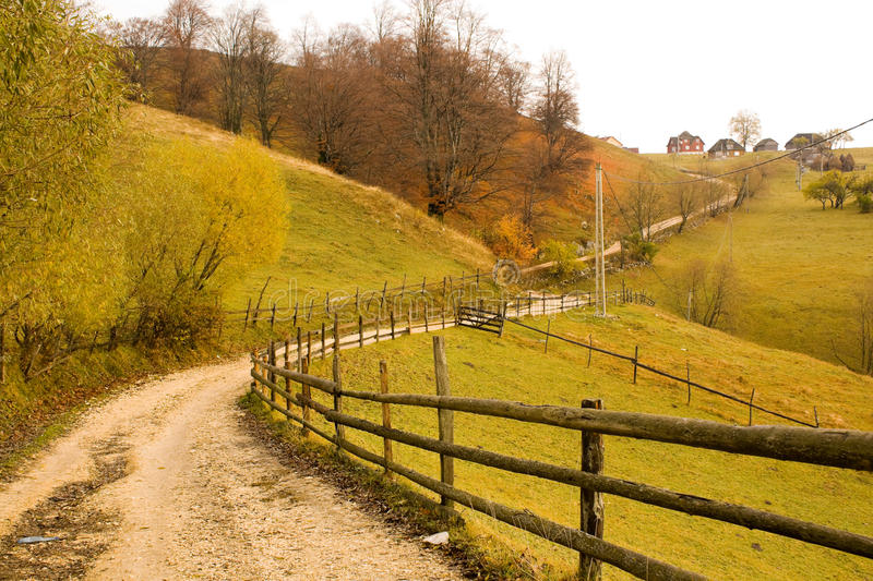 Country road. During autumn. In the picture there is a wood fence royalty free stock images