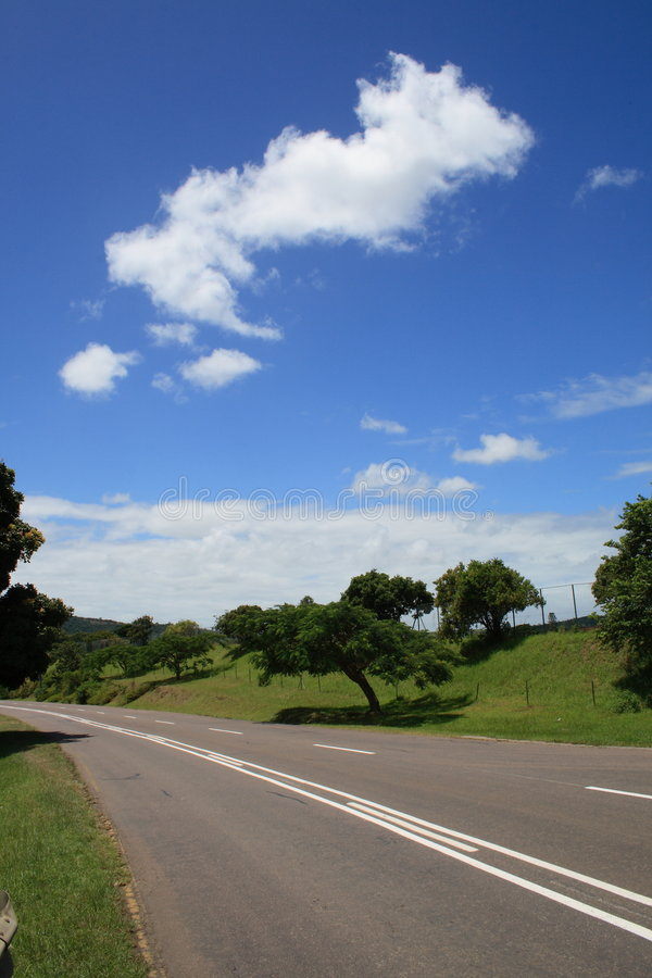 Country road. Blue sky and white clouds stock photography