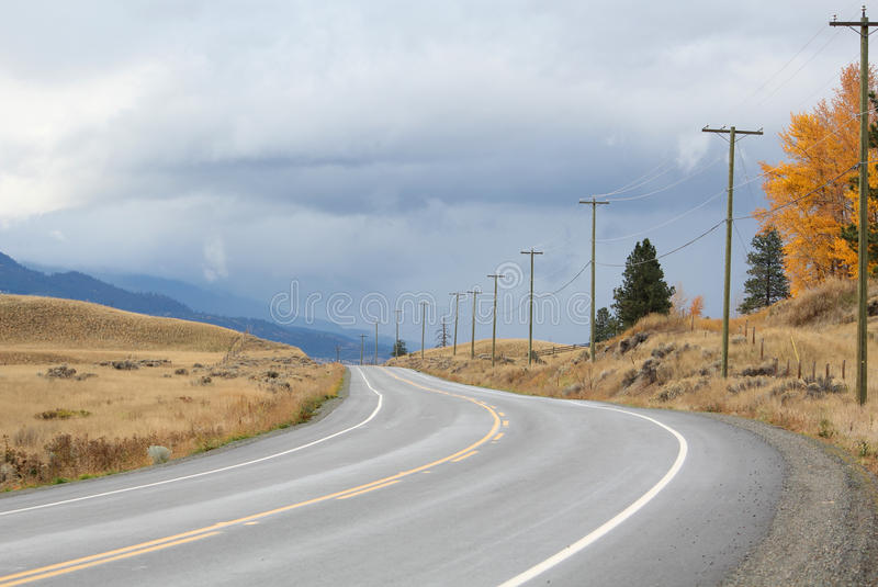 Country Road, British Columbia. Two lane blacktop under a threatening sky in the rural ranch country of the Nicola Valley, British Columbia, Canada royalty free stock photos