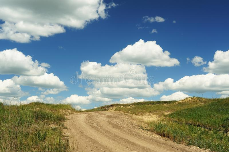 Country road ending in blue sky with big cumulus clouds royalty free stock photography