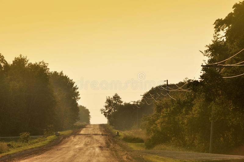 Country road in the evening. Country road under a hazy, orange evening sky royalty free stock images