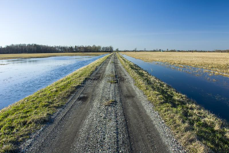 Country road and flooded fields. The gravel road through flooded meadows, horizon and blue sky royalty free stock photos