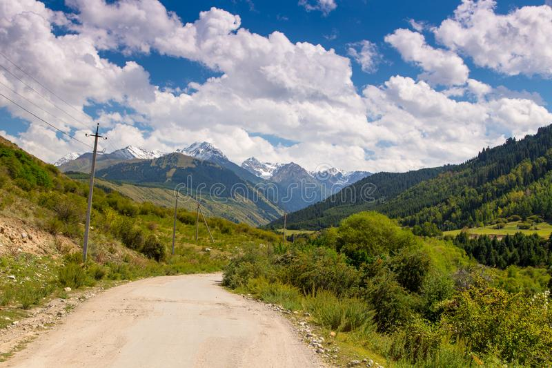 Country road high in the mountains. Tall trees, snowy mountains and white clouds on a blue sky. Kyrgyzstan Beautiful landscape royalty free stock image