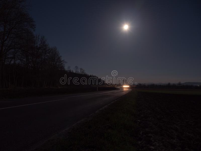 Country Road Illuminated by the Headlights of an Approaching Car. Winding Country Road Illuminated by the Headlights of an Approaching Car with Full Moon and royalty free stock photo