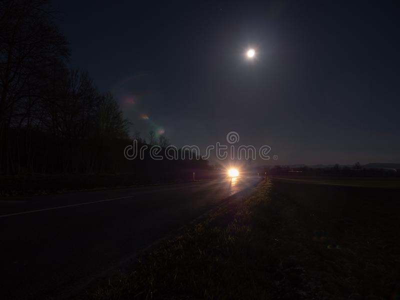 Country Road Illuminated by the Headlights of an Approaching Car. Winding Country Road Illuminated by the Headlights of an Approaching Car with Full Moon and royalty free stock image