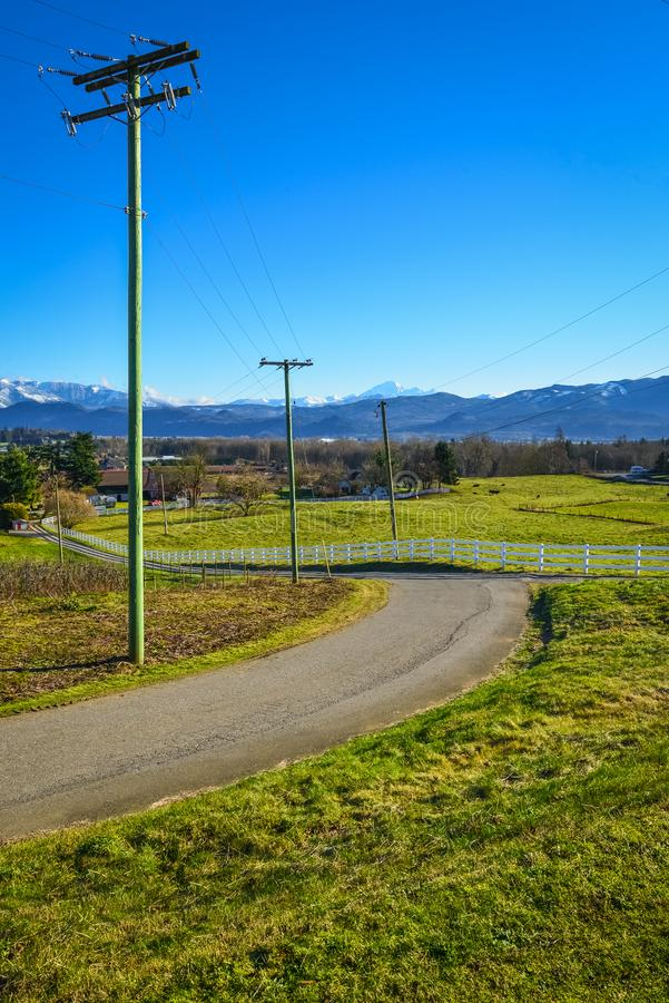 Country road leading to a cattle farm on winter season. Rural road with power posts on the side and mountain view background royalty free stock photography