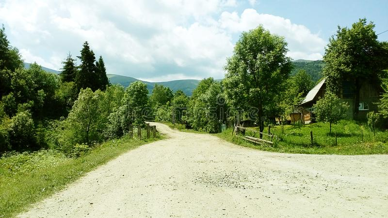Country road in the mountains on clear summer day. Country road in the mountains on a clear summer day royalty free stock images