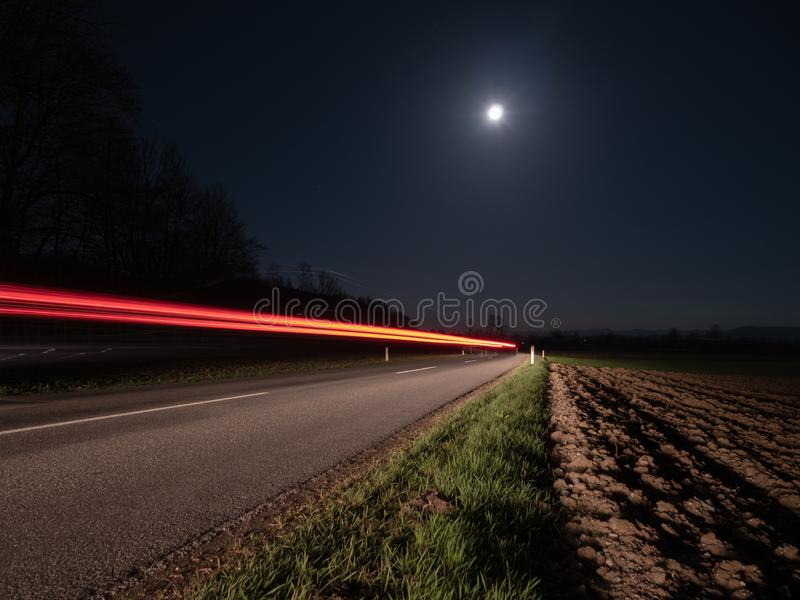 Country Road at Night Illuminated by a Passing Car. With Full Moon and Red Light Trails - Long Exposure royalty free stock image