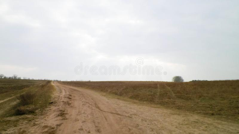 Country road, offroad in northern Poland. Country road, offroad in northern Poland countryside. Copy space on cloudy sky royalty free stock image