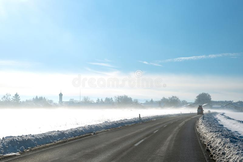 Country road in rural wintry landscape with morning fog stock photos