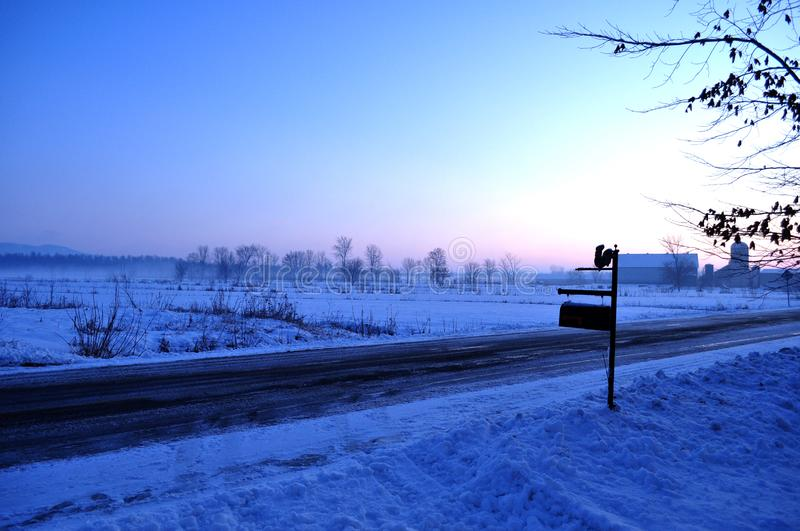 Country road and snowy plains, mail box and farm stock images