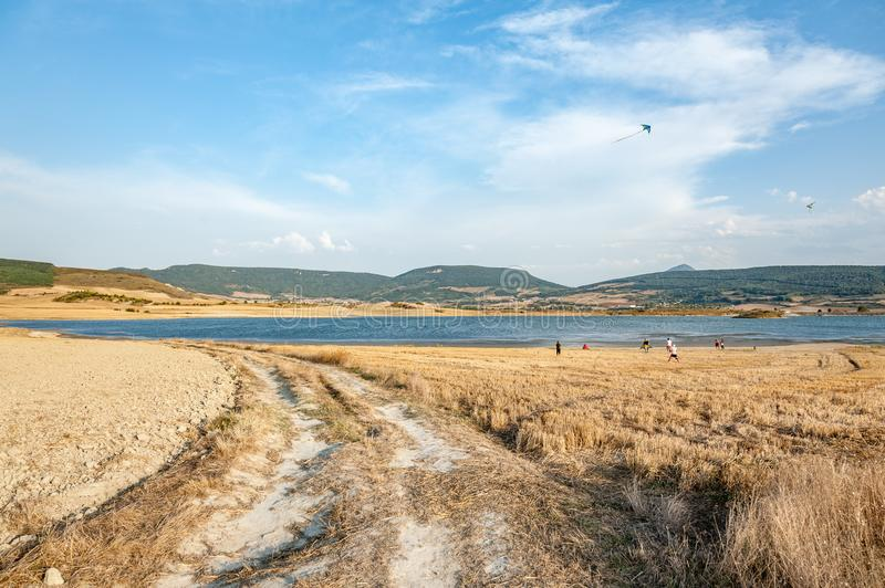 Country road towards the lake in Navarra, Spain. People launch kites stock photography